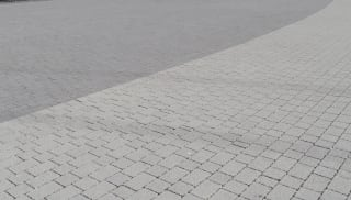 Charcoal block paving outside arena.