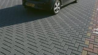 Black car driving in a car park.