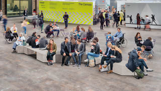Members of the public sitting on a bench.