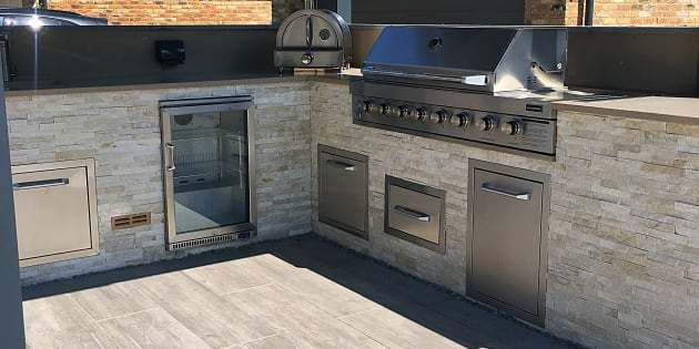 Outdoor kitchen featuring pizza oven and barbeque