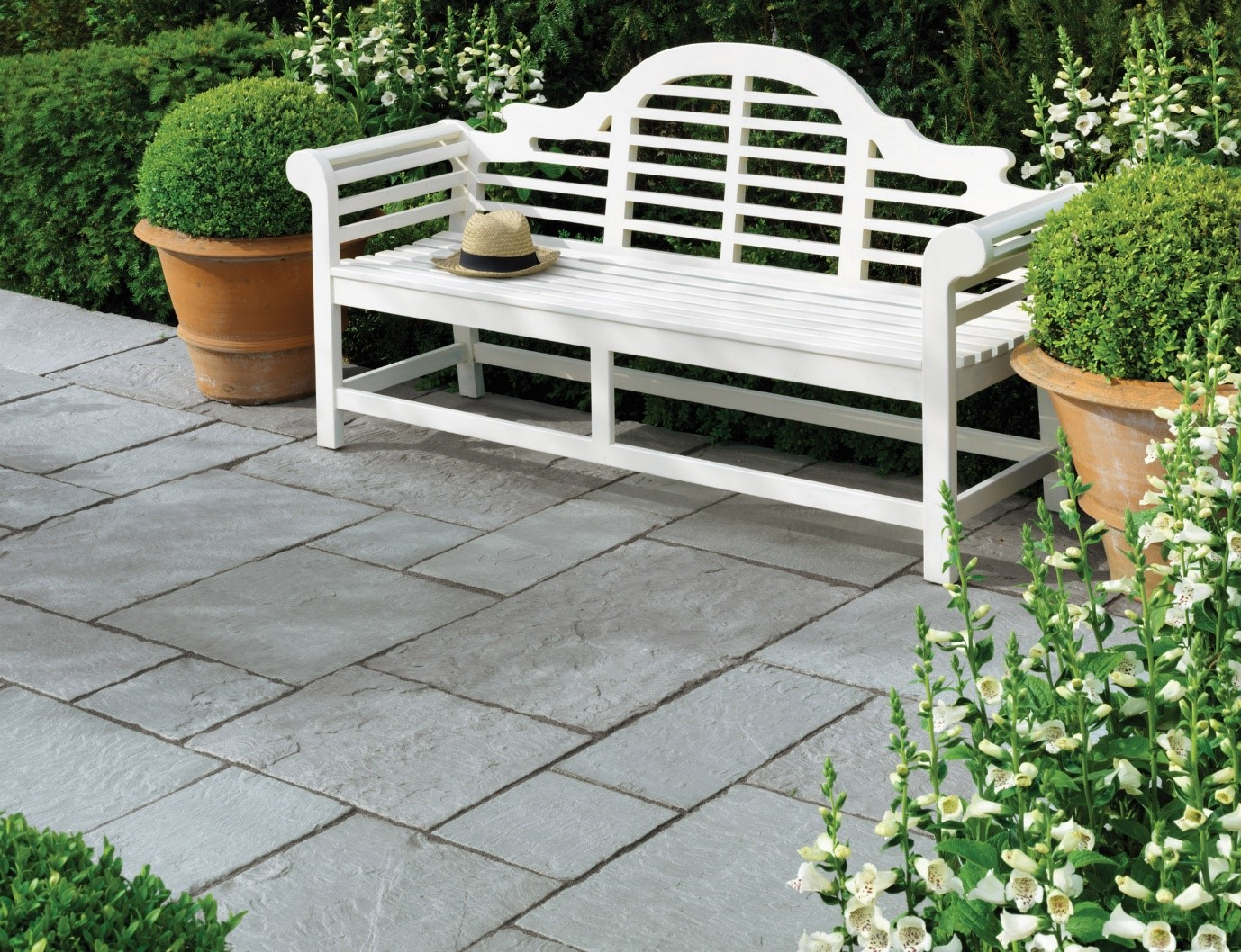 white bench on grey paving in a patio area
