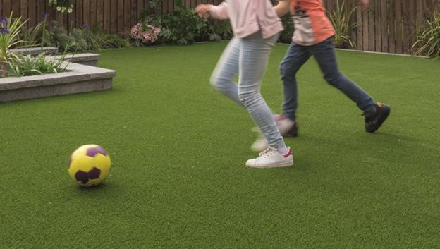 Two children playing football on artificial grass