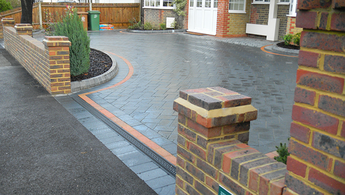 Dark grey paving laid in front of a house on a driveway.