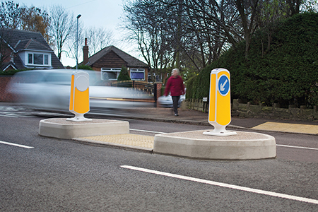 Concrete traffic island used as a pedestrian crossing in the middle of the road
