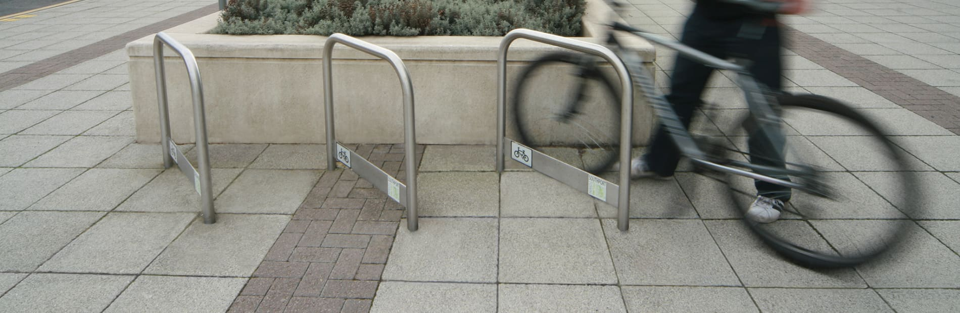 cycle rack stainless steel with a man attaching his bike
